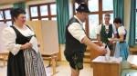 Menschen in Trachten bei der Stimmabgabe